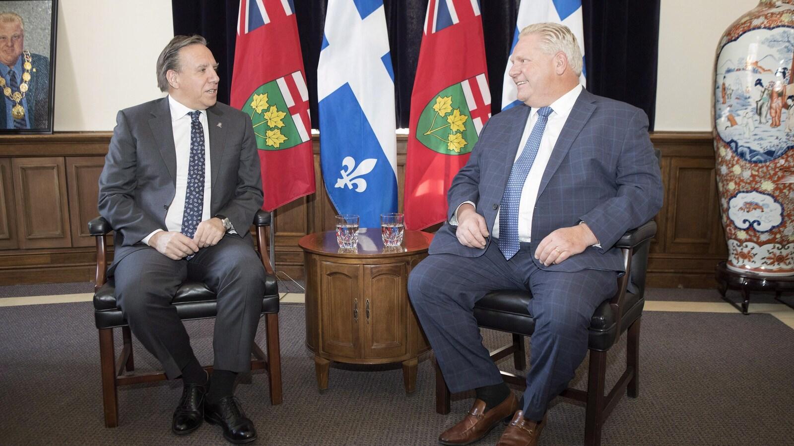 Deux hommes assis devant des drapeaux de l'Ontario et du Québec discutent
