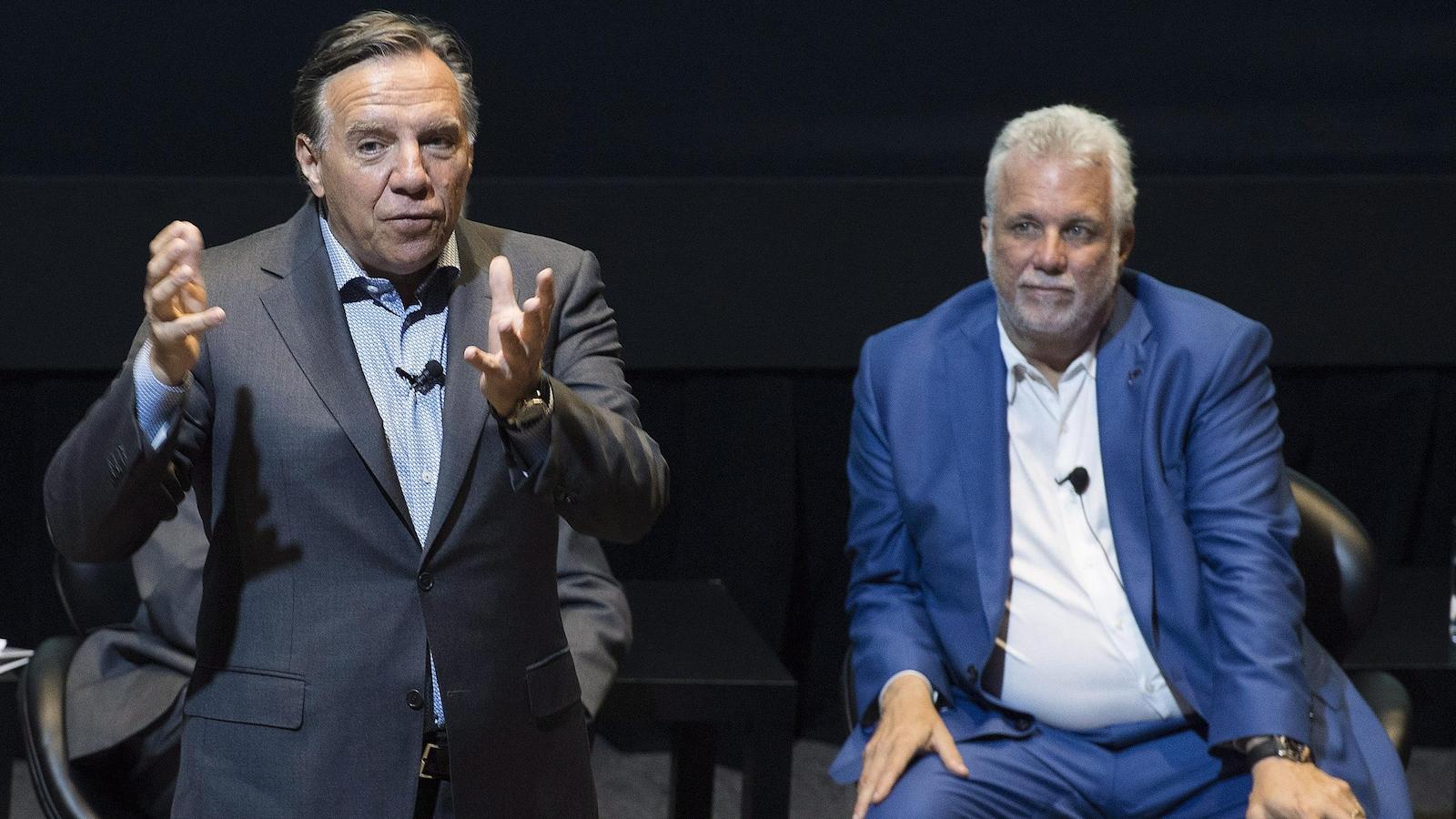 Le premier ministre Philippe Couillard écoute le chef de la CAQ, François Legault, lors d'un événement organisé par l'Institut du Nouveau Monde, le 17 août 2018.