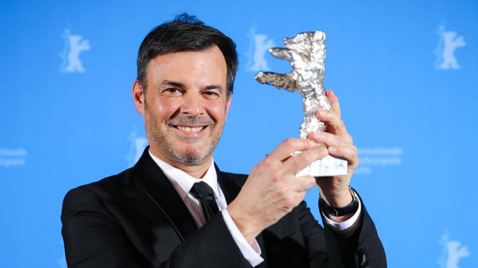 François Ozon tient une statuette en forme d'ours.