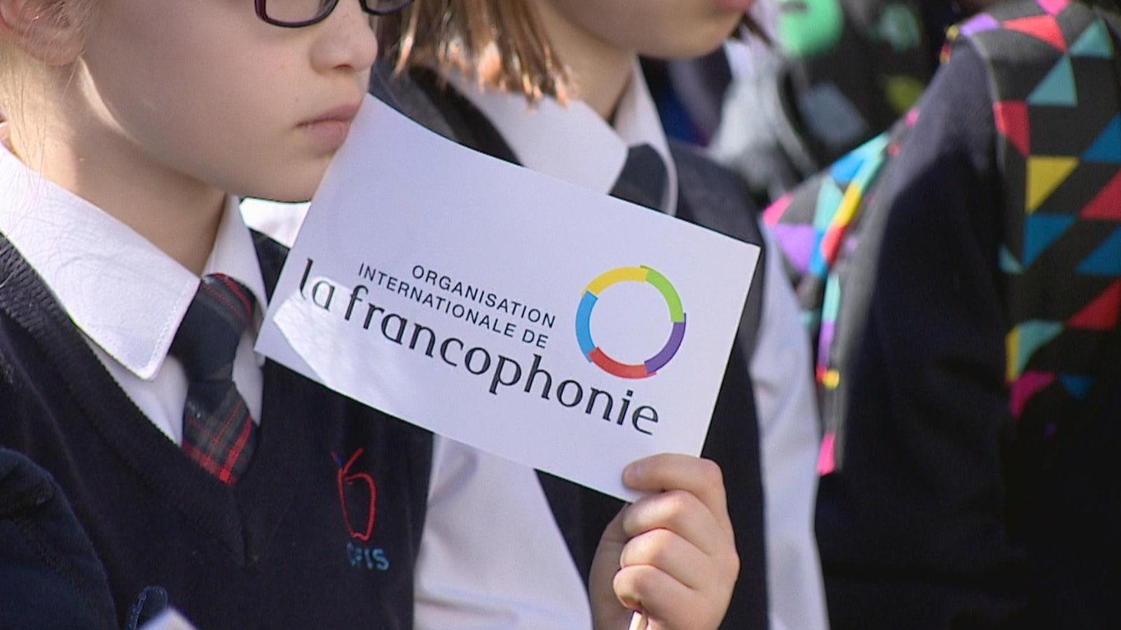 Vue sur une jeune fille qui porte des lunettes. Elle tient dans ses mains un drapeau où il est écrit: organisation internationale de la francophonie.