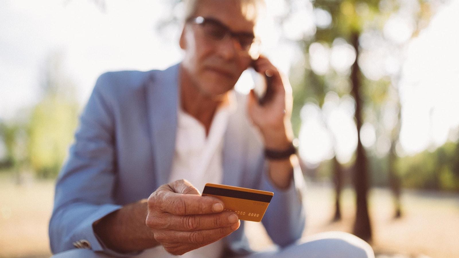 Un homme donne son numéro de carte de crédit au téléphone.