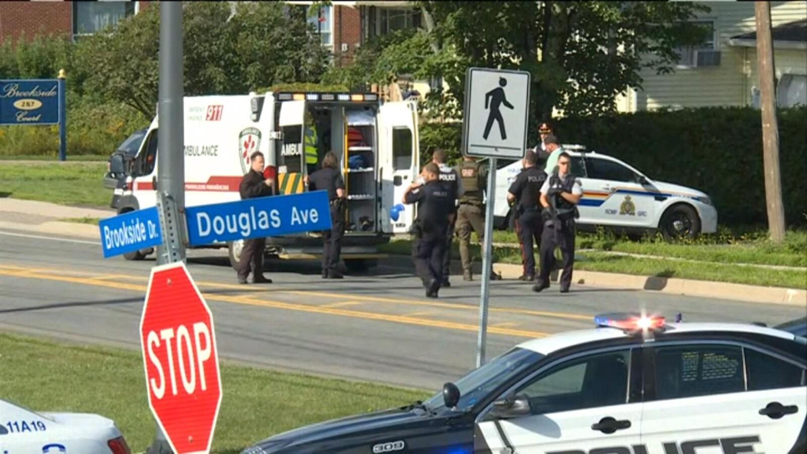 Des policiers déployés à l'arrière d'une ambulance.