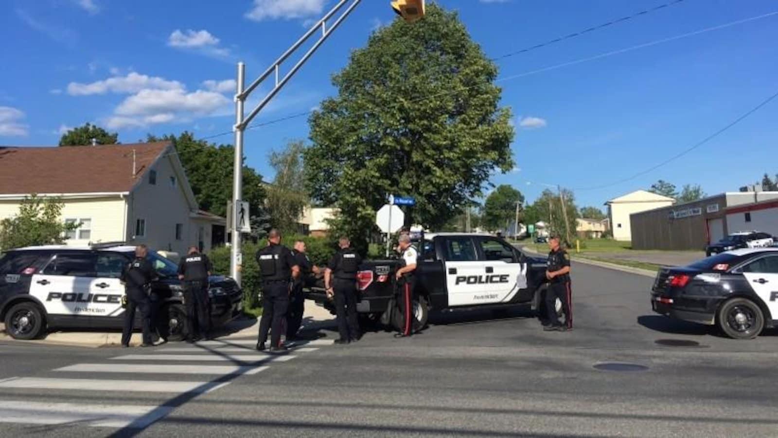 Des policiers devant des véhicules des forces policières de Fredericton.