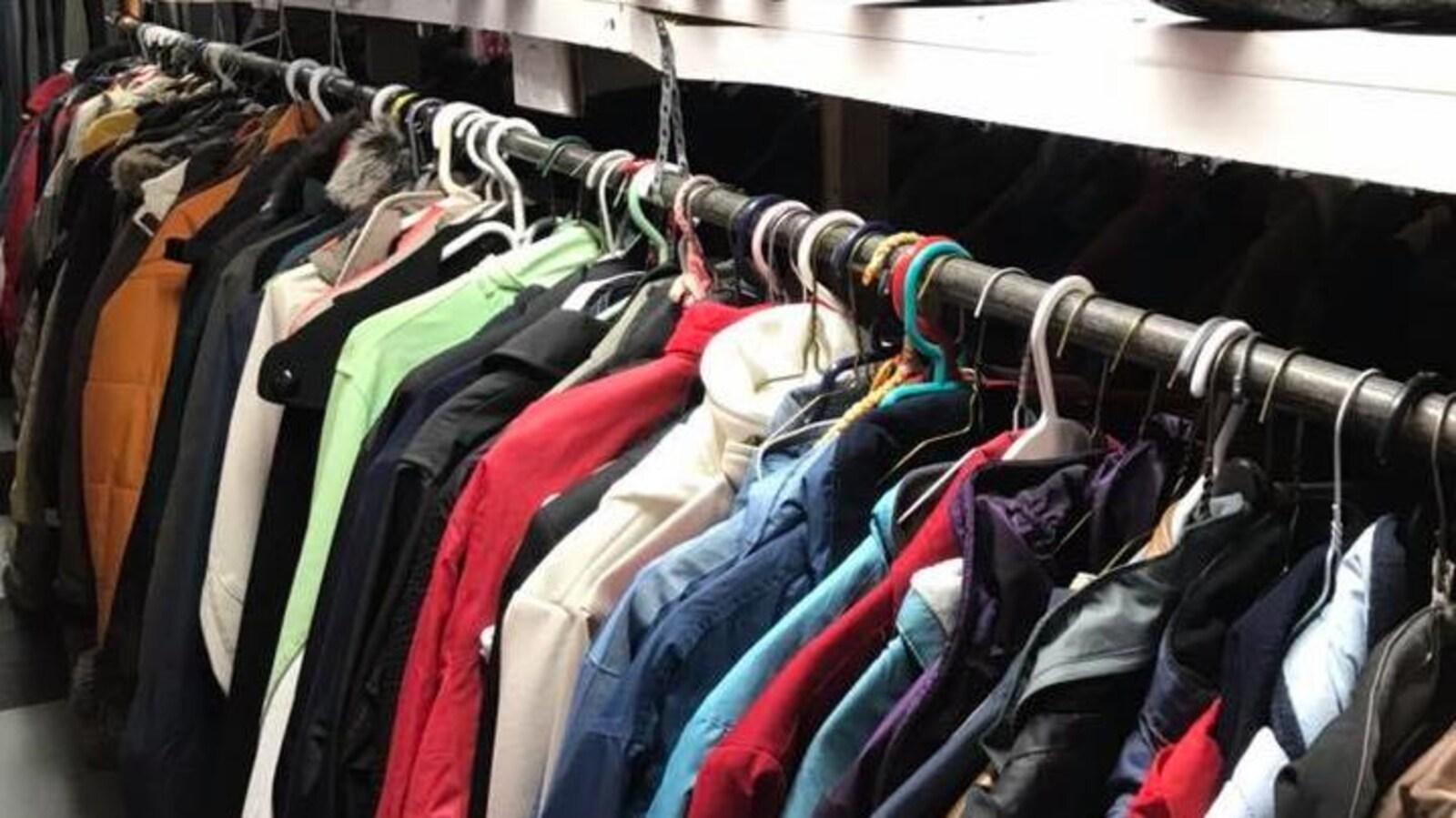 Des vêtements sont disposés dans une friperie.