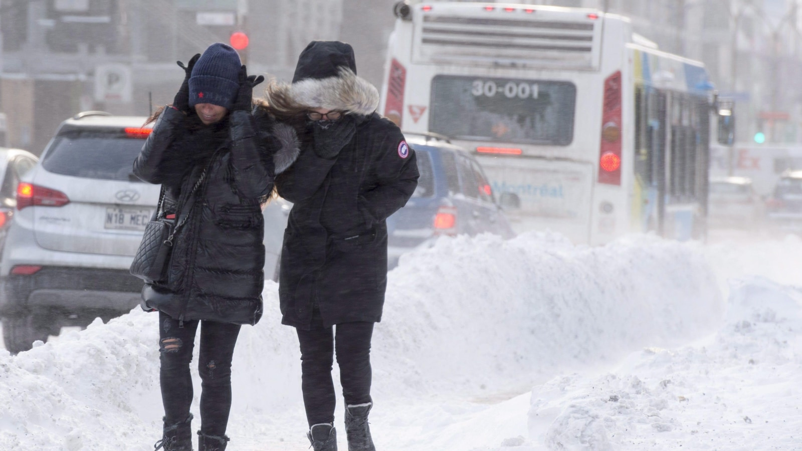 Deux personnes marchent sur un trottoir enneigé et se protègent du vent glacial. Elles sont lourdement habillées.