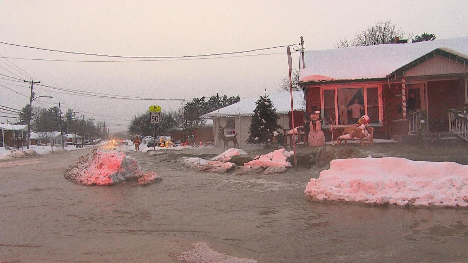 De l'eau s'écoule en grande quantité dans une rue et sur le terrain d'une résidence unifamiliale.