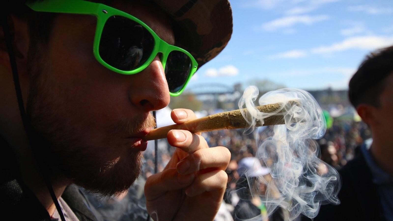 Un participant au 4/20 de Vancouver fume un joint.