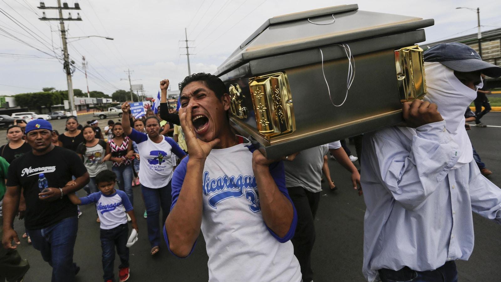 Des gens transportent un cercueil en criant dans la rue.