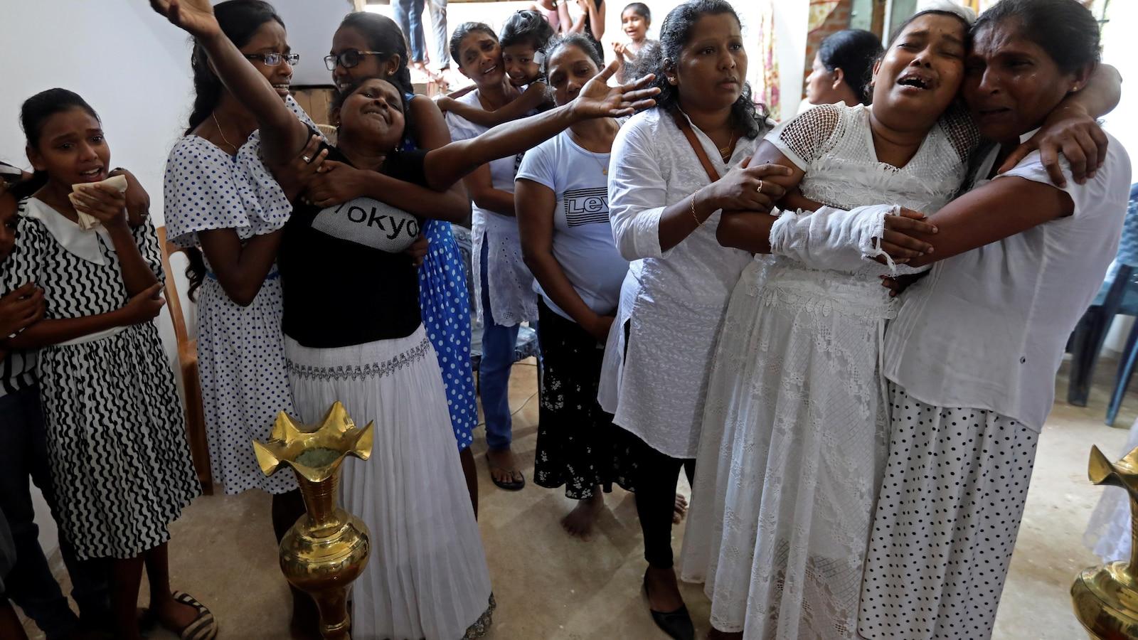 Des femmes habillées en blanc assistent aux funérailles. Plusieurs sont en pleurs.