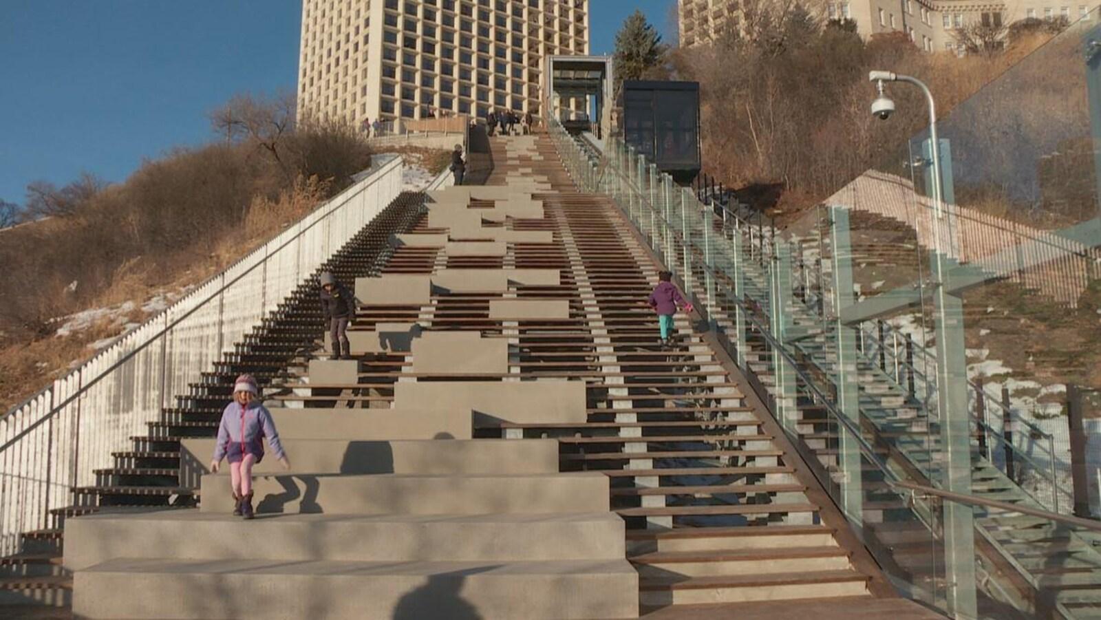 Le funiculaire fonctionne pendant que des enfants montent et descendent un escalier qui se trouve à ses côtés.