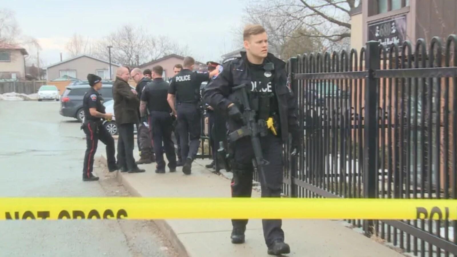 Des policiers sont rassemblés sur un trottoir, un officier au premier plan tient une arme d'assaut, tous se trouvent derrière un ruban de sécurité.
