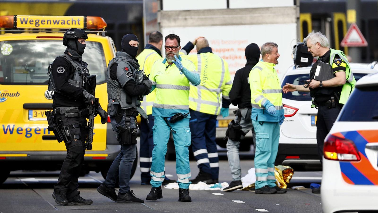 Les forces de l'ordre, cagoulées et armées, discutent avec les services d'urgence, en vêtements d'intervention jaune fluo.
