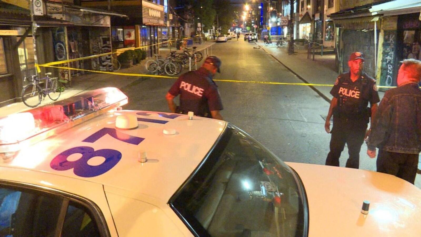 Photo d'une autopatrouille, d'une banderole jaune et de policiers bloquant une rue.