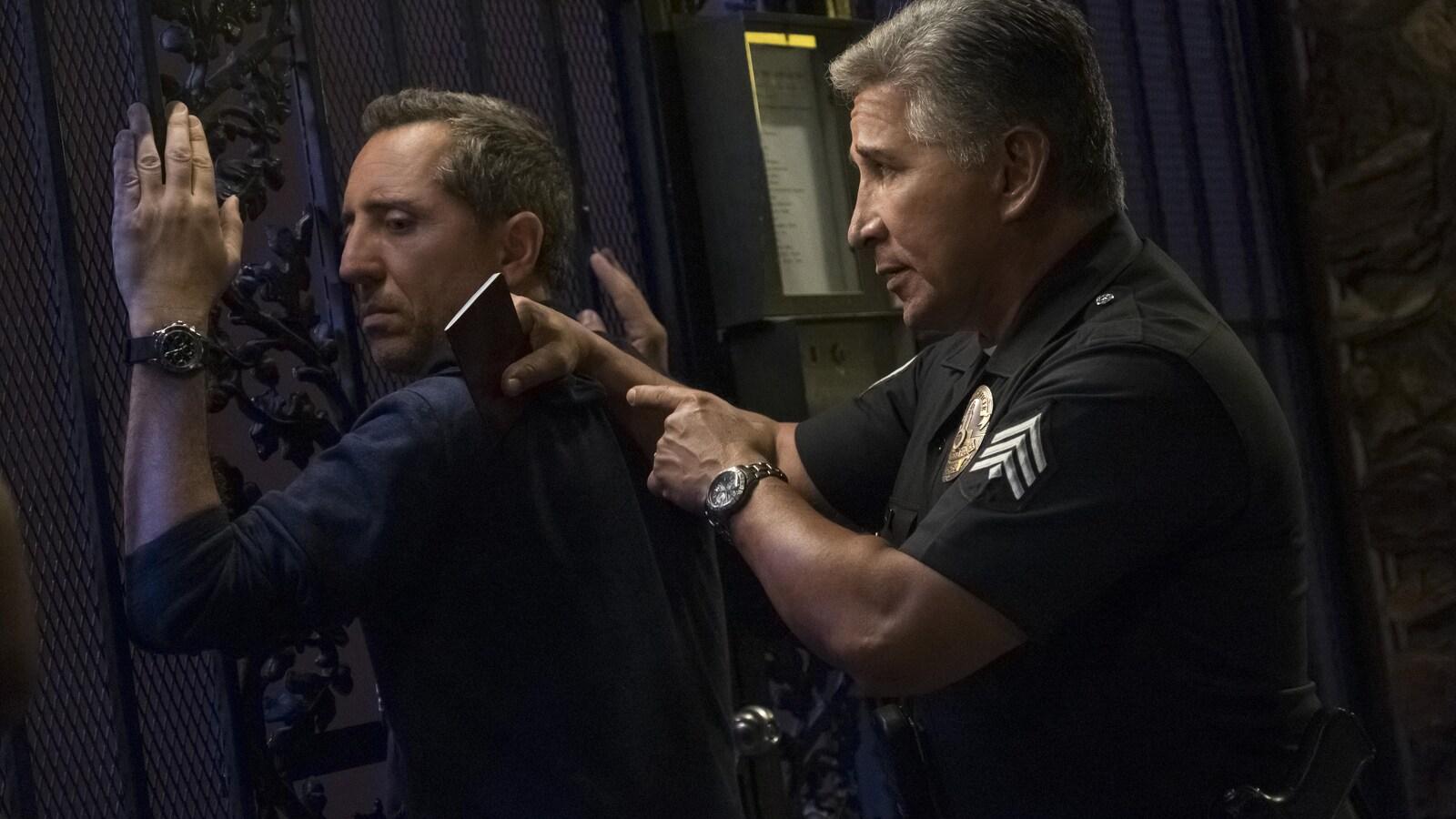 L'humoriste se tient les mains en l'air et est maintenu au mur par un gardien de sécurité.