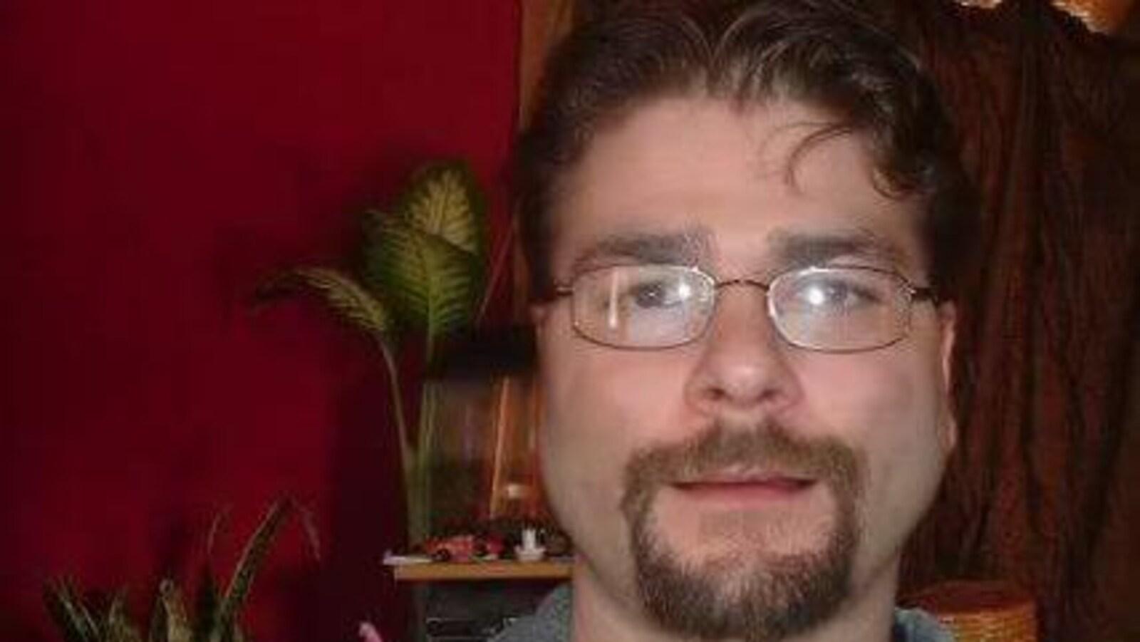 Un homme avec des lunettes et un bouc se trouve devant un mur rouge et regarde droit devant lui.