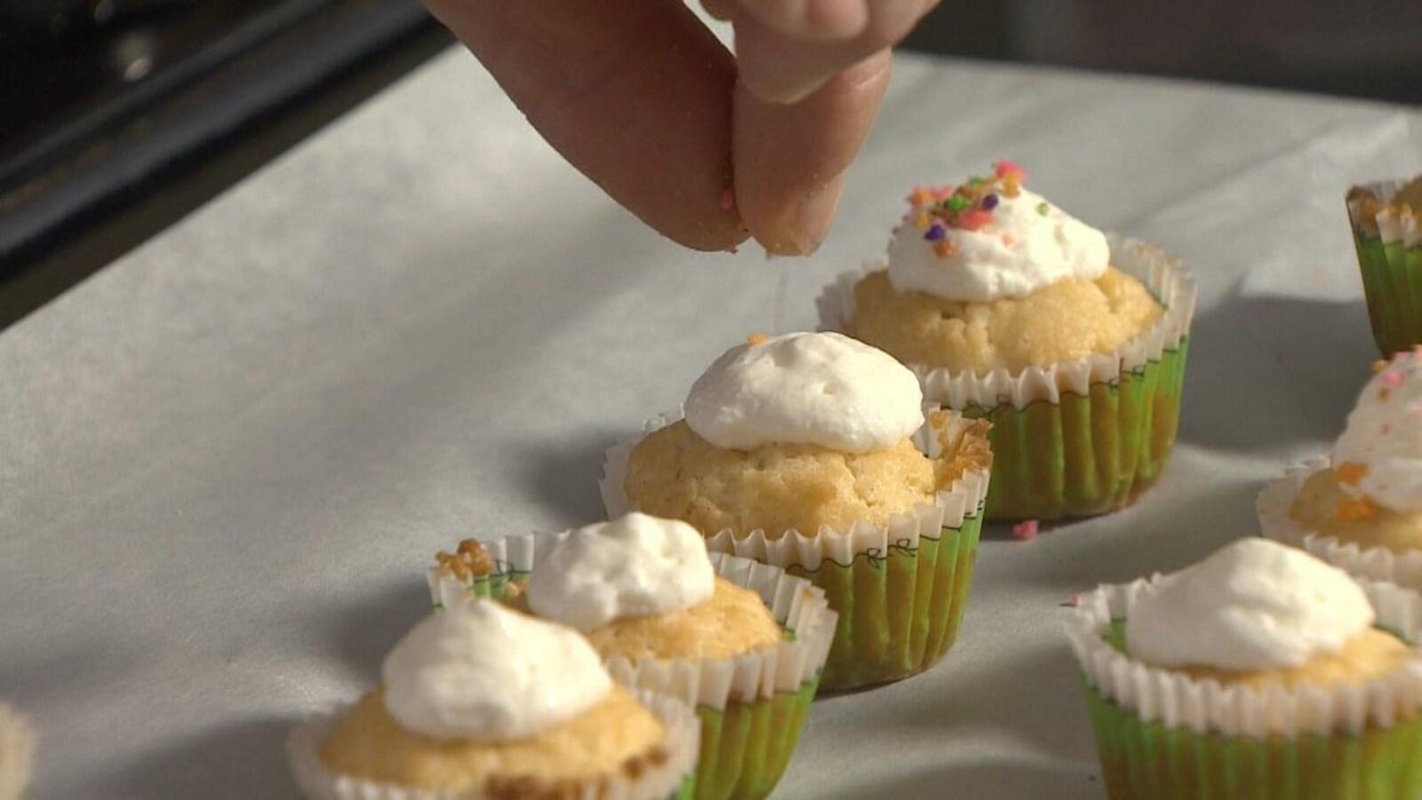 Mme Guimond met un glaçage à la vanille sur ses petits gâteaux.