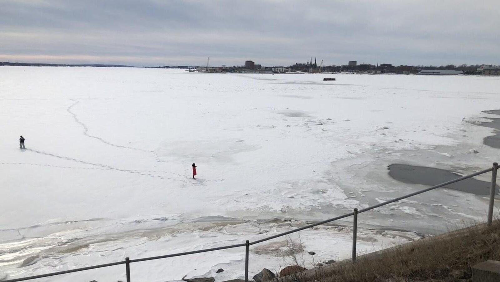 Deux personnes sur la glace avec le centre-ville de Charlottetown en arrière-plan.