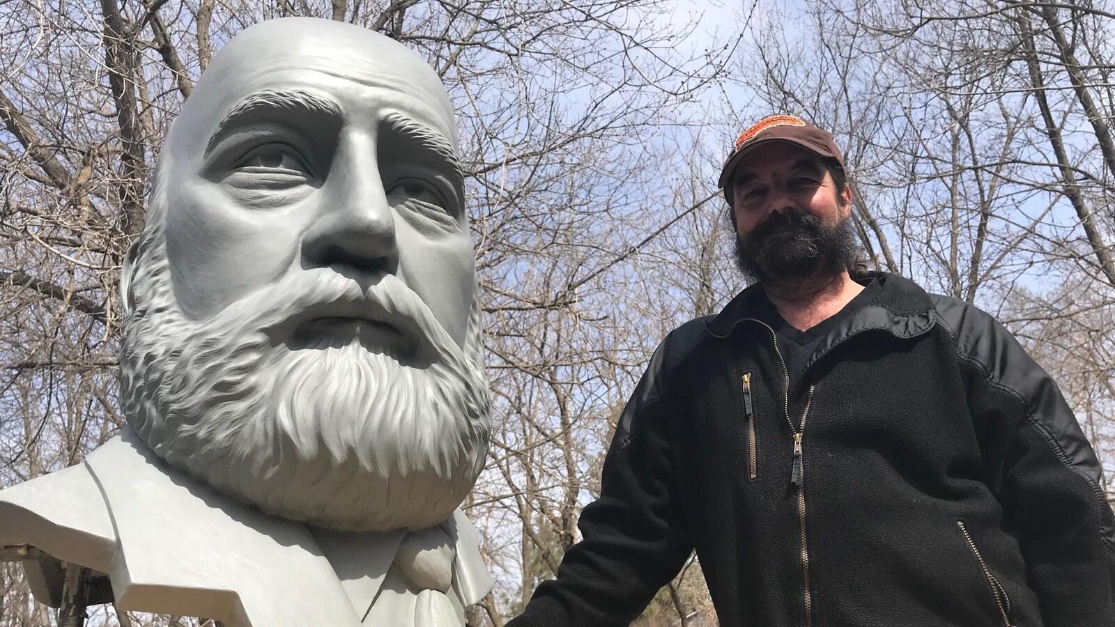 Le buste d'un homme qui doit faire partie d'un monument qui n'est pas encore terminé, etl'artiste qui l'a sculpté.