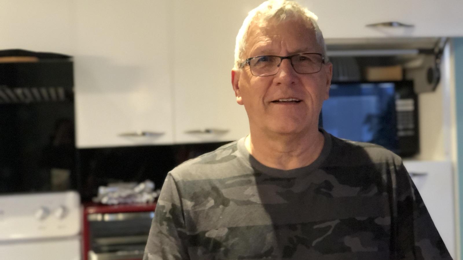 Gilbert Richard debout dans la cuisine de sa maison.