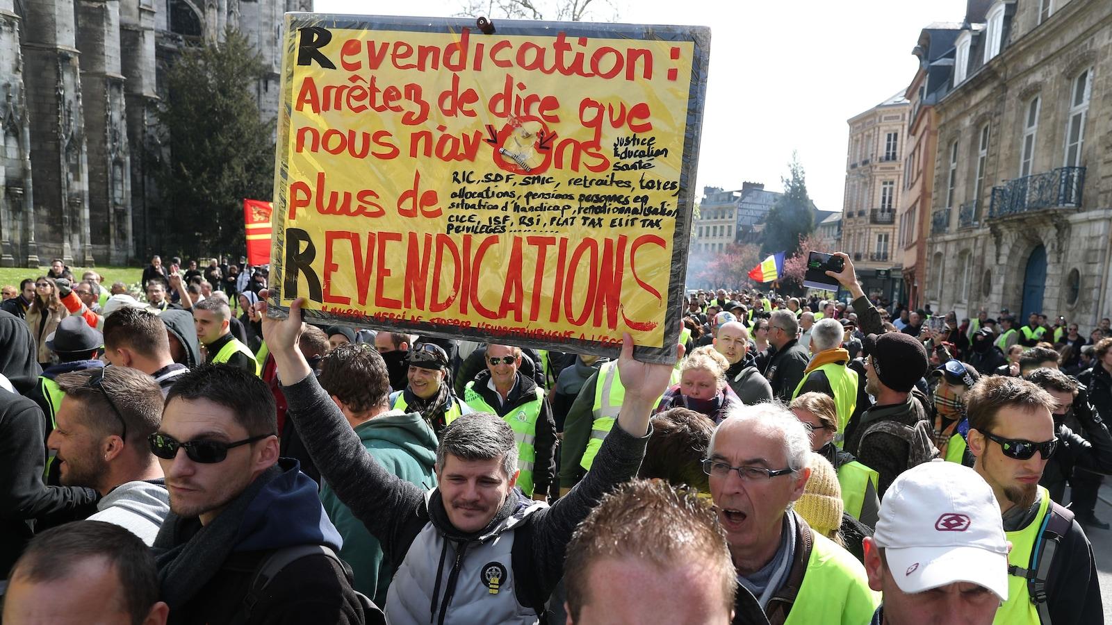 Une foule de manifestants, dont un tient une pancarte.