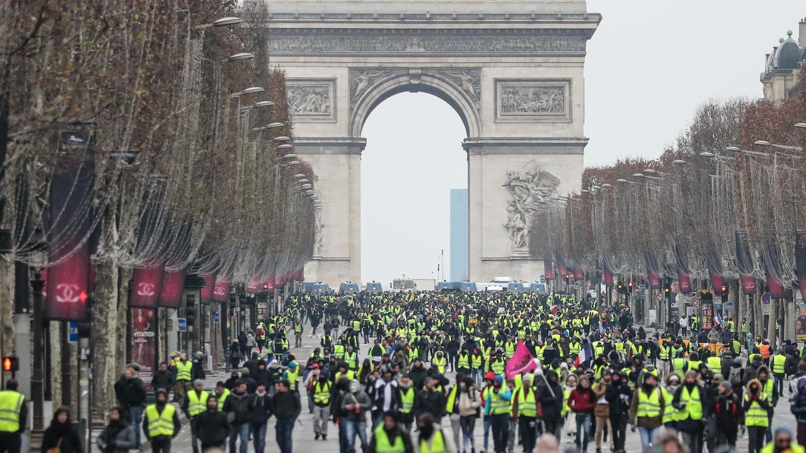 Plusieurs centaines de personnes marchent à Paris, plusieurs portant un gilet jaune. À l'arrière se dresse l'Arc de Triomphe.