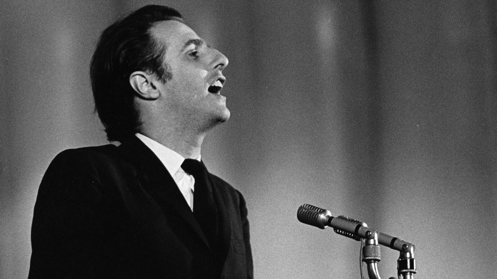 Sur une scène, Gilles Vigneault, chante, un micro sur pied devant lui.