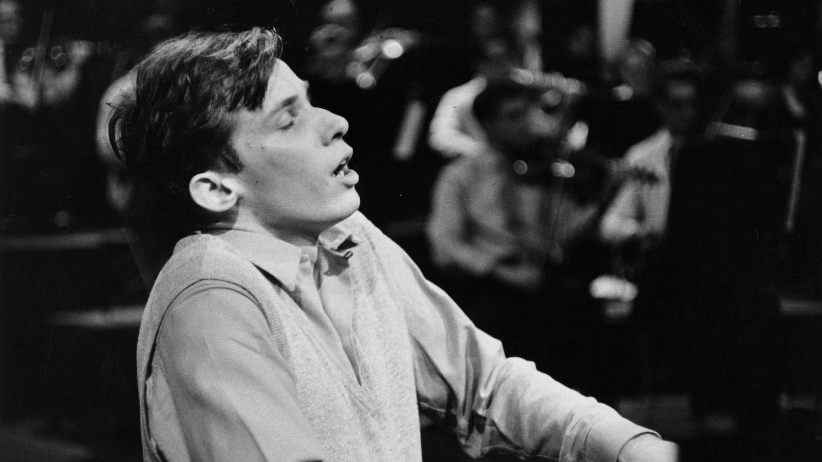 Glenn Gould semble en extase devant son piano.