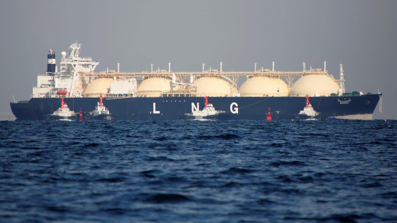Des remorqueurs guident un navire de GNL sur une mer plate à l'est de Tokyo