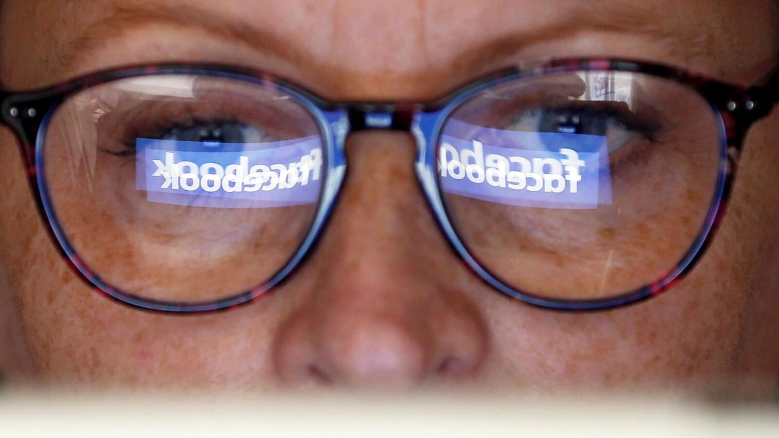 Le reflet du logo de Facebook sur les lunettes d'une femme.