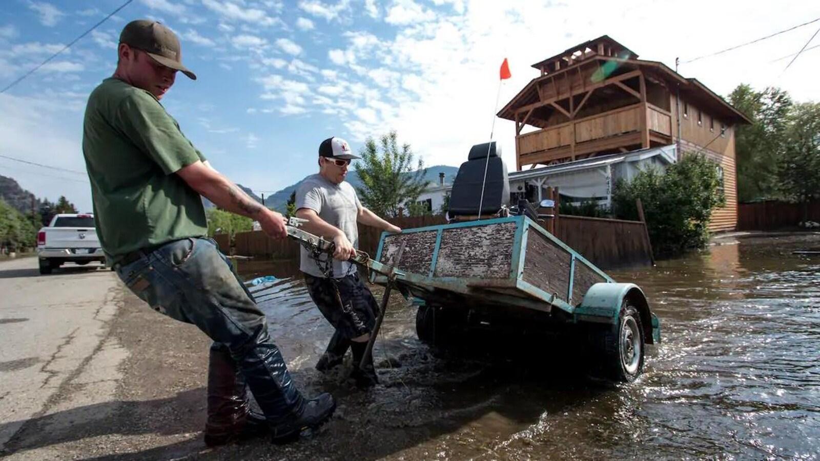 Deux hommes tirent manuellement une remorque vers une route qui est séparée d'une maison en arrière-plan par une zone inondée.