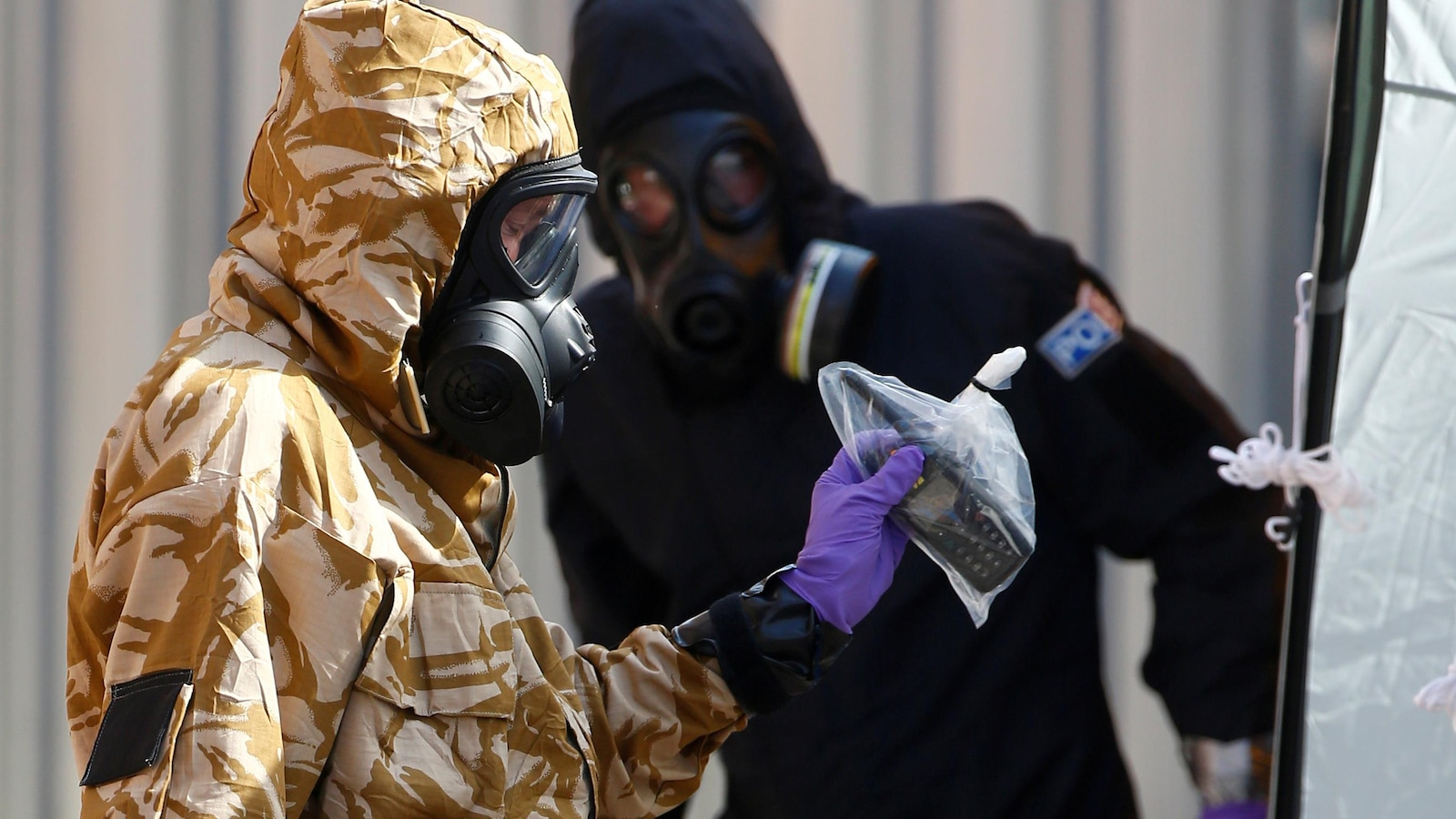 Deux hommes en habit de protection, un d'entre eux tient un téléphone dans un sac de plastique.