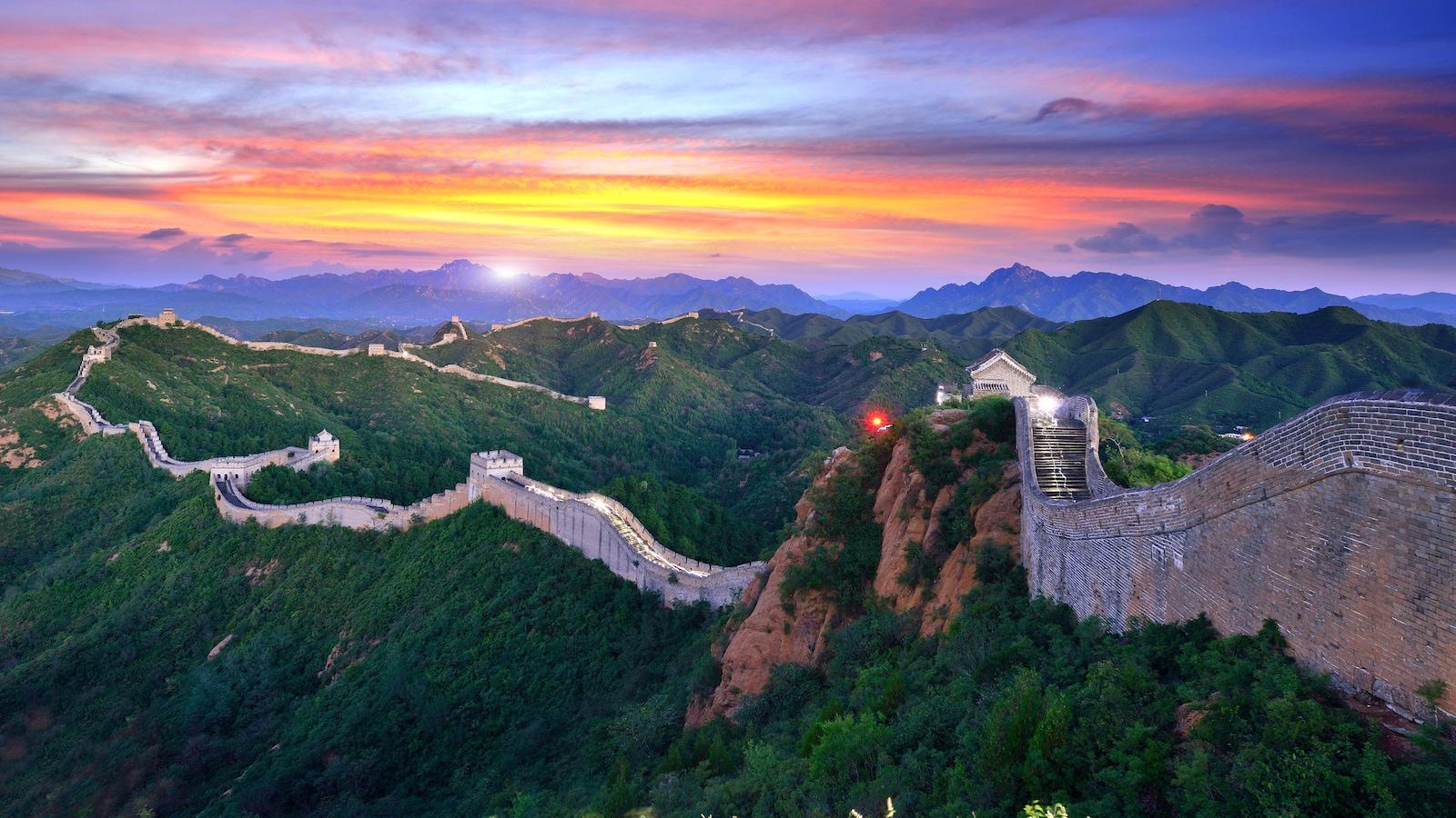 La Grande Muraille de Chine devant un coucher de soleil.