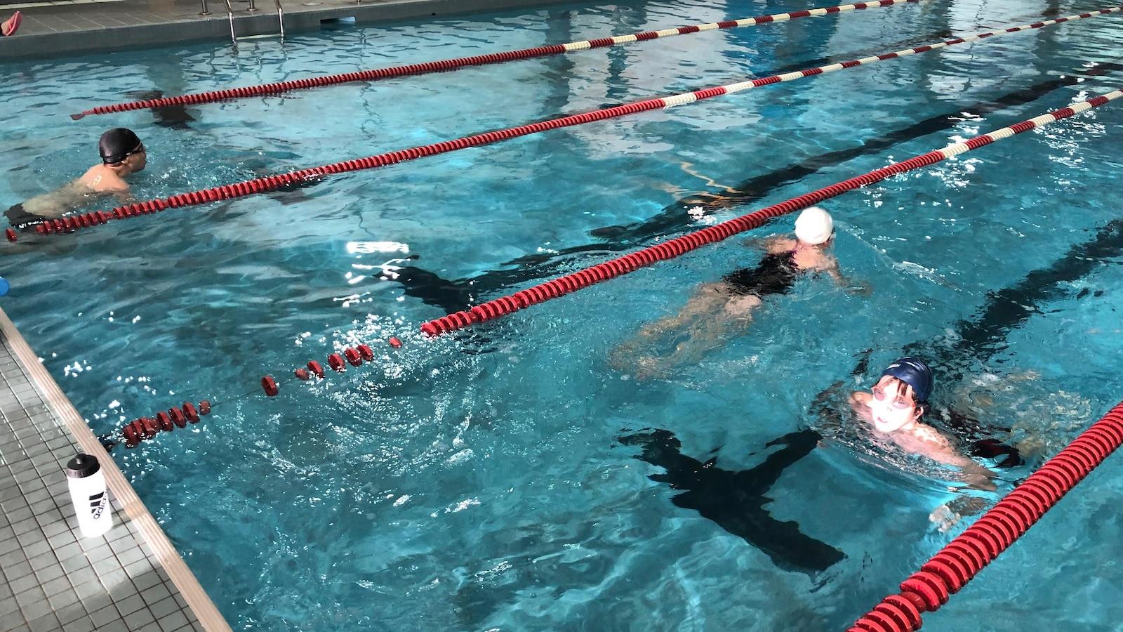 Deux nageurs se croisent dans un couloir de la piscine.