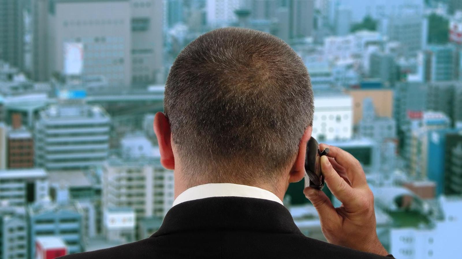 Un homme au téléphone regarde par la fenêtre d'un gratte-ciel.