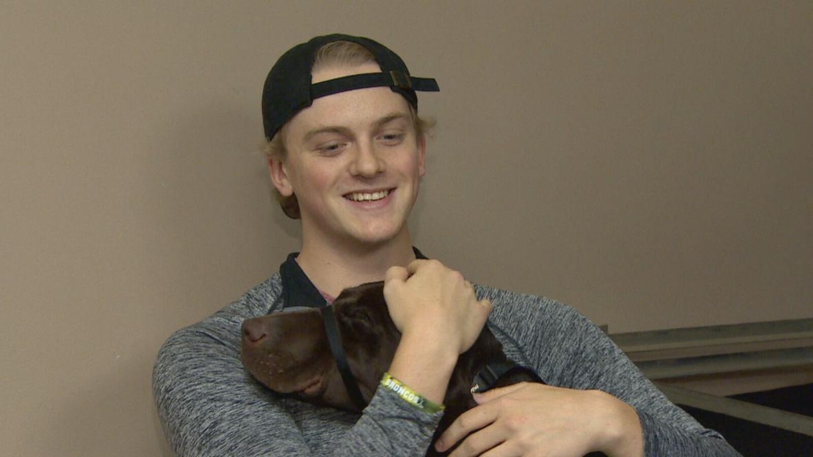 Un jeune homme portant une casquette à l'envers serre un chien dans ses bras.