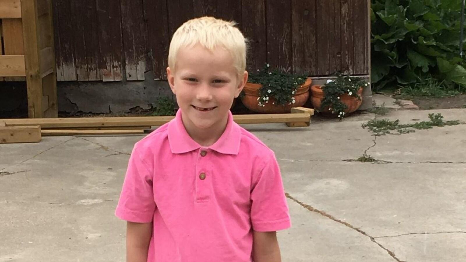 Un petit garçon blond vêtu d'un polo rose, à l'extérieur.