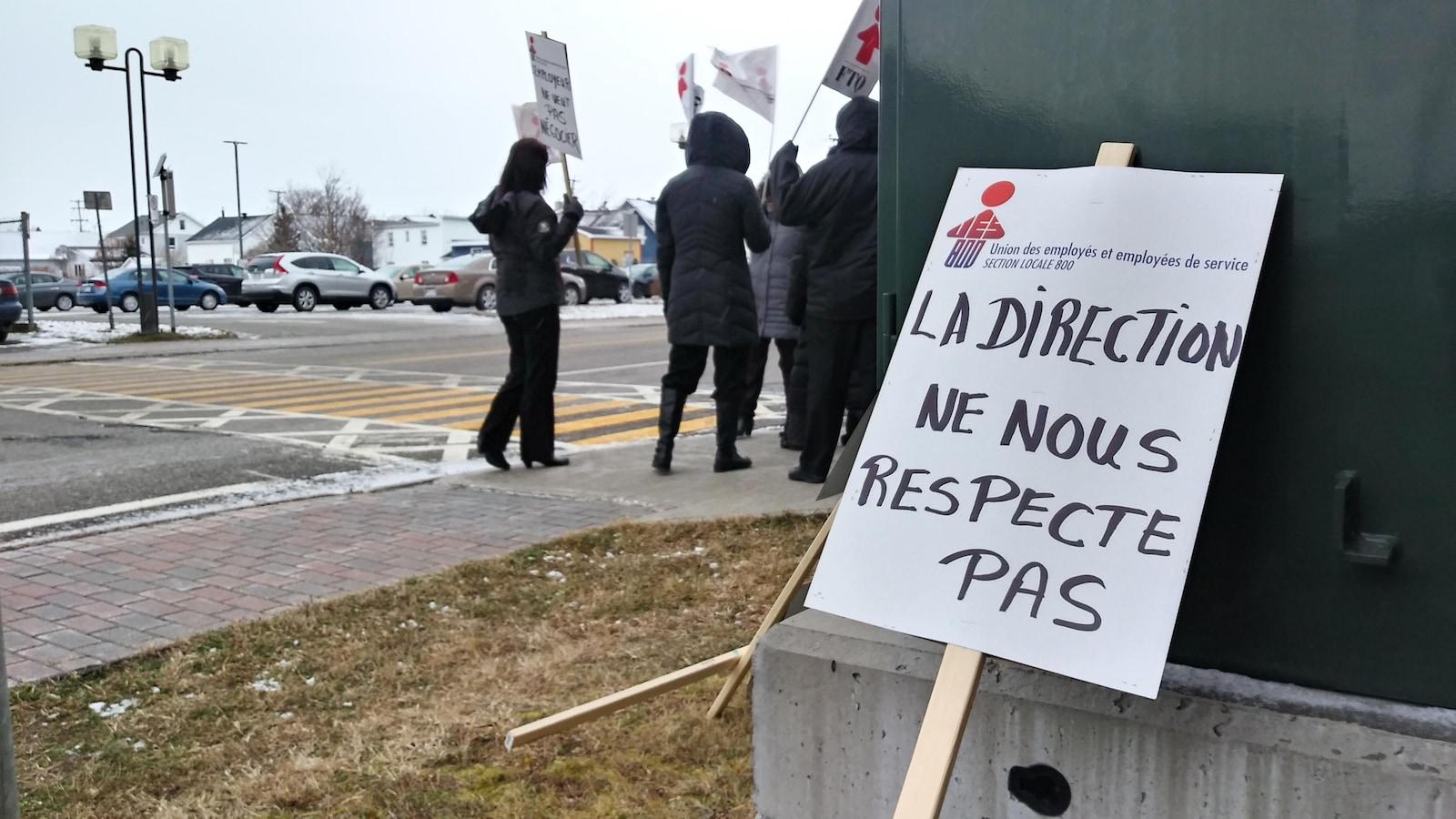 Travailleurs qui manifestent dehors.Pancarte. « La direction ne nous repecte pas. »