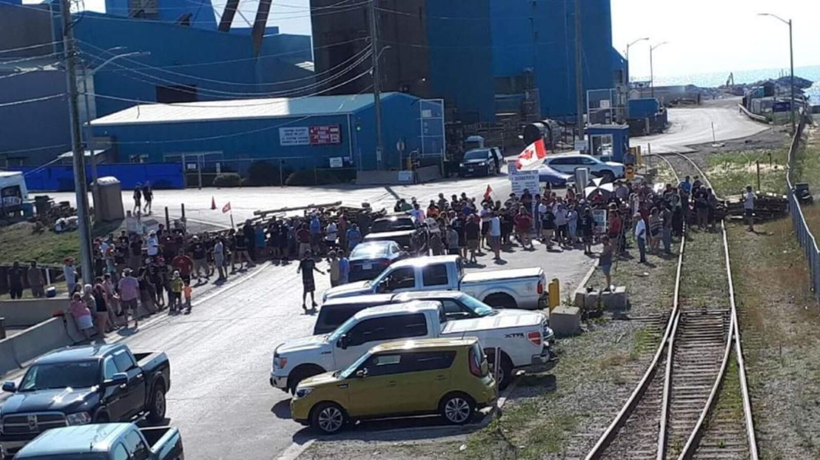 Des gens et des véhicules bloquent une entrée.