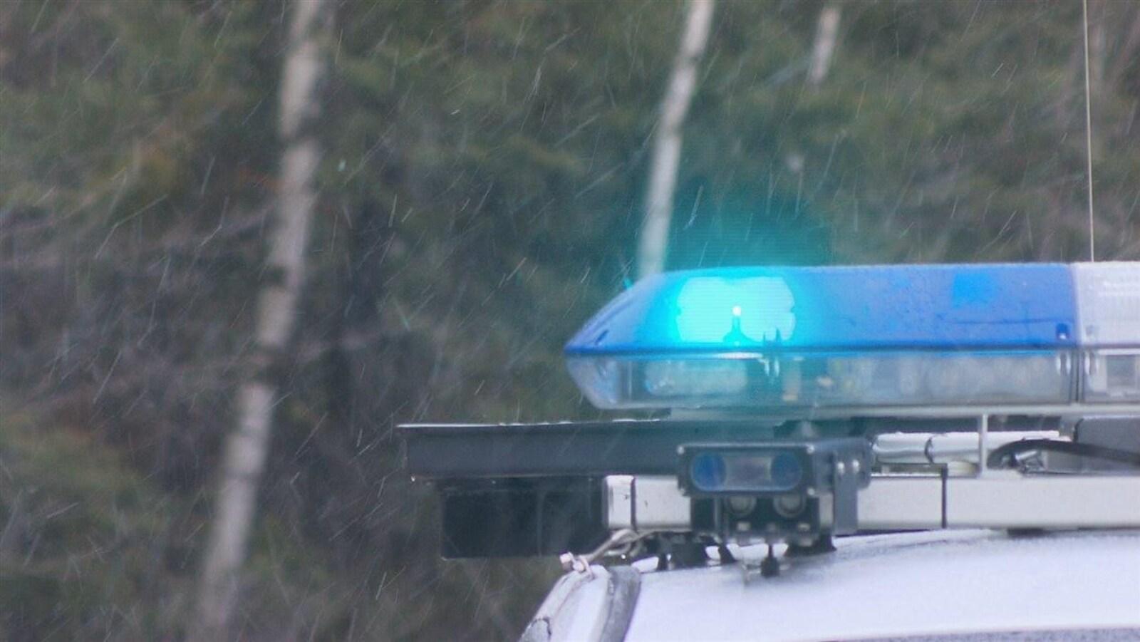 Gyrophares dans la neige et devant un boisé