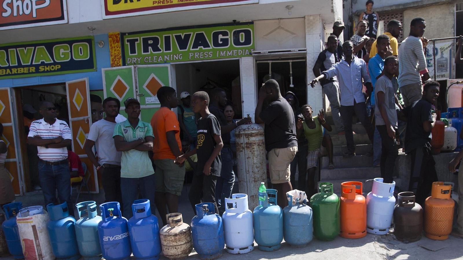 Une vingtaine de personnes, principalement des hommes, font la file devant des magasins avec leurs bidons de propane dans une rue commerciale de Port-au-Prince.
