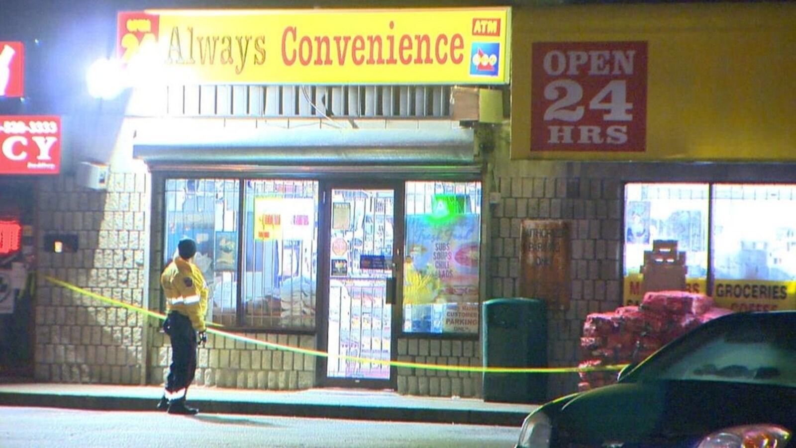 Photo de l'enseigne jaune du dépanneur; un policier monte la garde devant l'édifice.