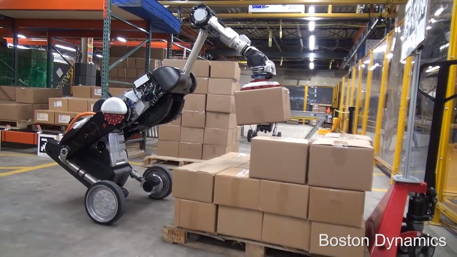 Une photo du robot Handle tenant une boîte au bout de son bras articulé dans un entrepôt.