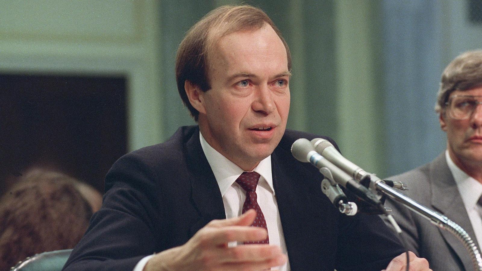 Une photographie d'archive datant de 1989 illustre James Hansen parlant devant deux micros.