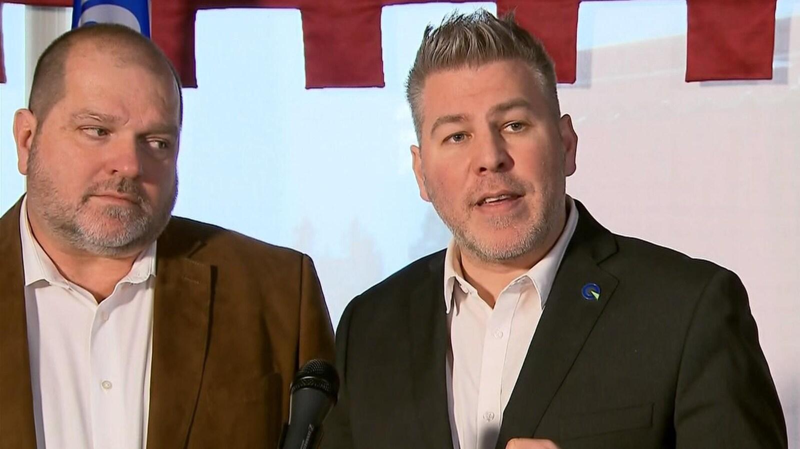 Deux hommes répondent aux questions des médias en conférence de presse.