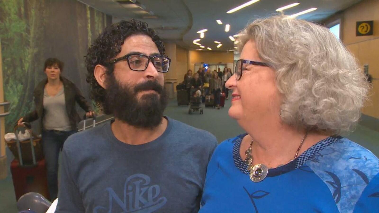 Un homme avec des cheveux frisés noirs, une moustache et une barbe touffue et des lunettes à monture noire regarde avec amour une femme âgée blonde qui le regarde avec un sourire béat.