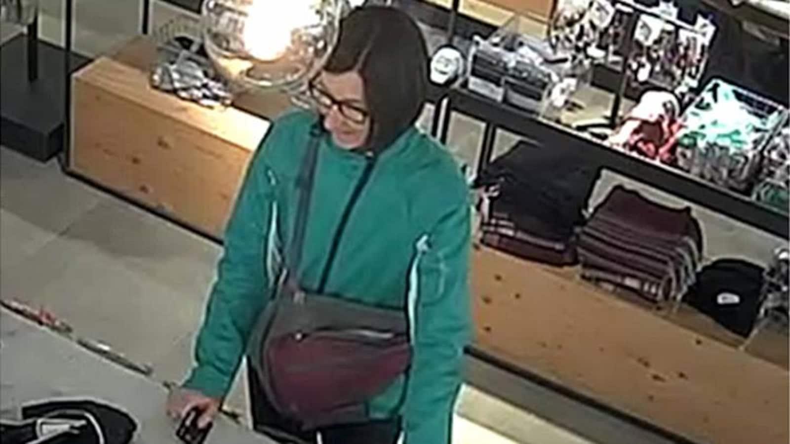 Image tirée d'une caméra de surveillance démontrant une femme devant un comptoir de magasin, prête à payer.