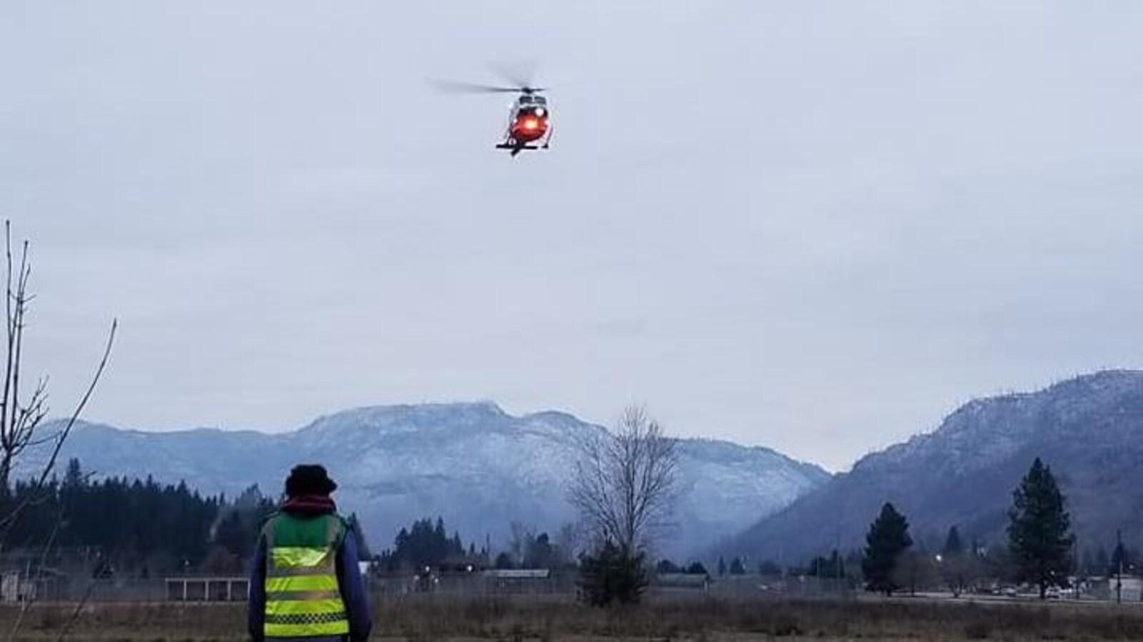 Un hélicoptère du Service des ambulanciers de la Colombie-Britannique survole un paysage montagneux
