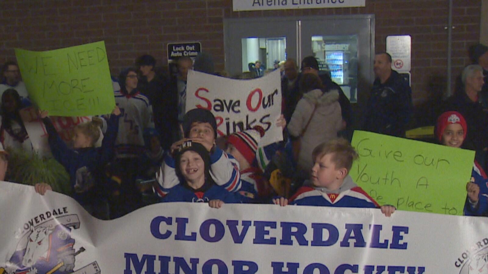 Des enfants souriants et portant des chandails de hockey tiennent une bannière portant le nom de l'association de hockey pour enfants de Cloverdale.
