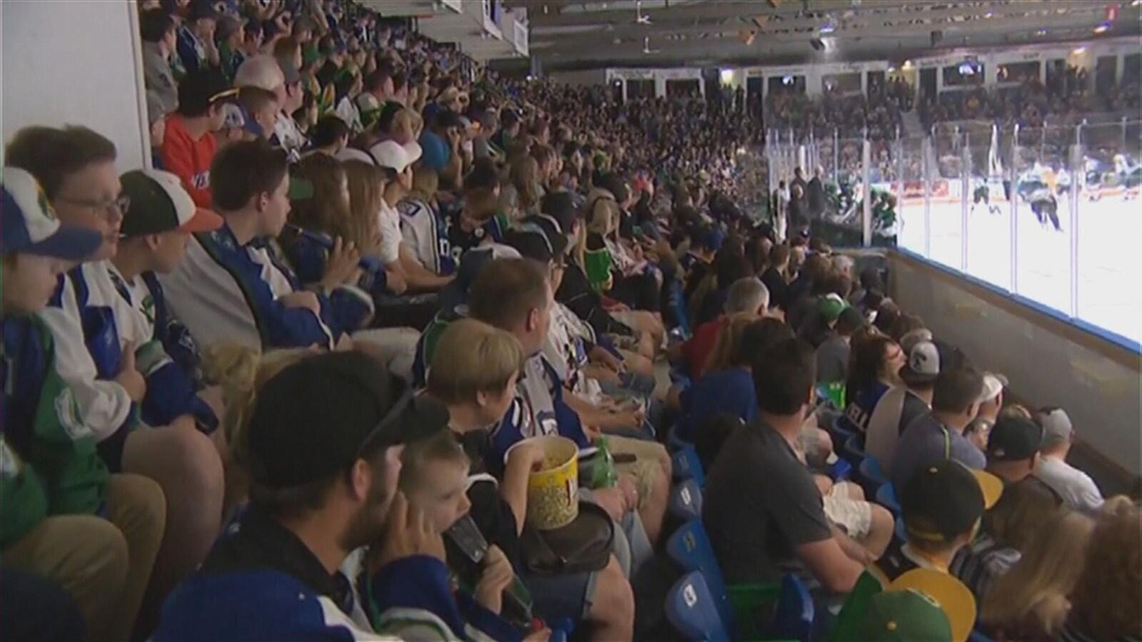 La foule porte des chandails de hockey et regarde attentivement la glace où se déroule le match.