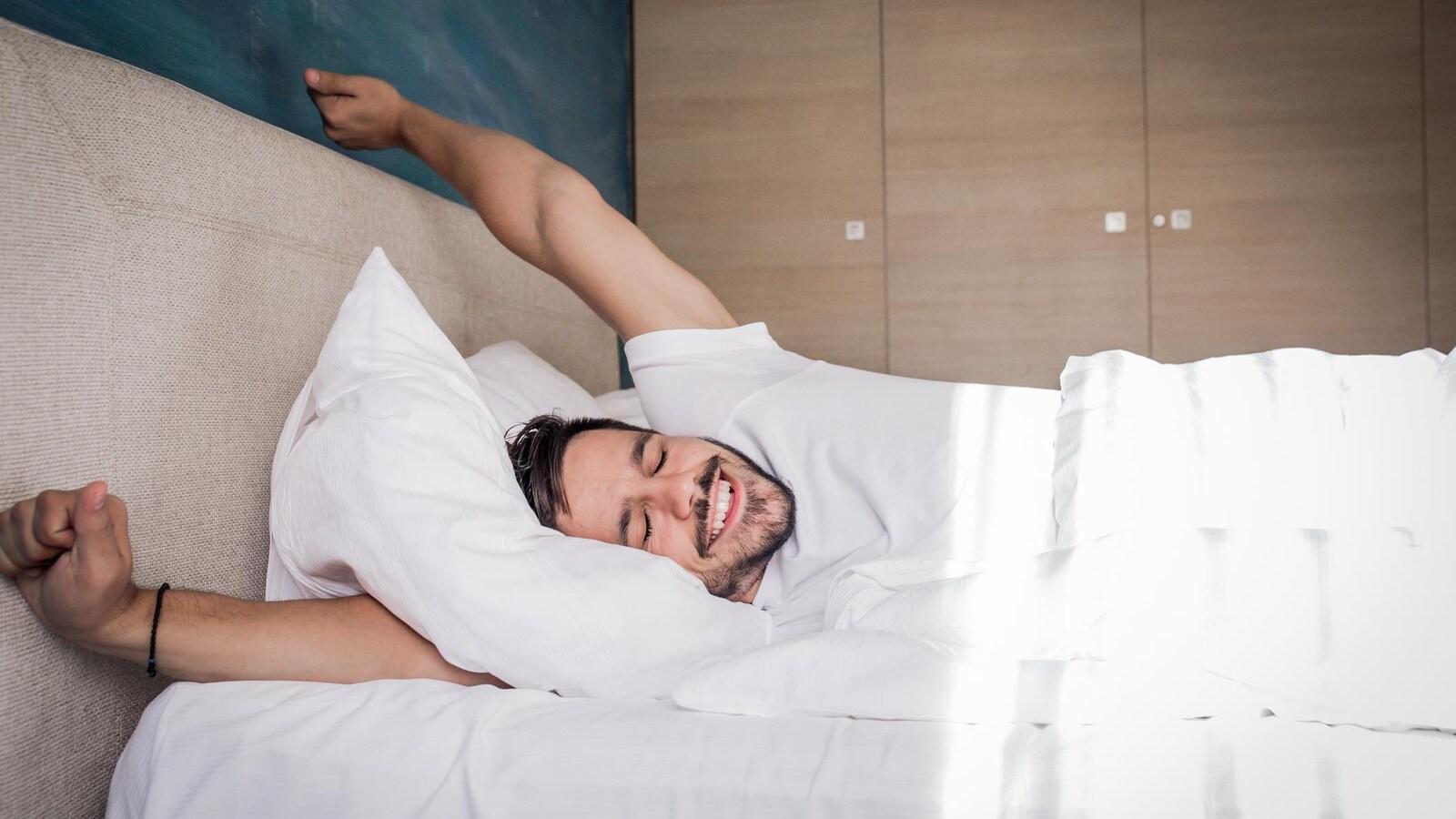 Un homme s'étire dans un lit.